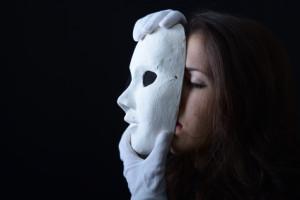 brunette girl holding a white theatrical mask